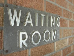 Photo of a Waiting Room Sign on a brick wall